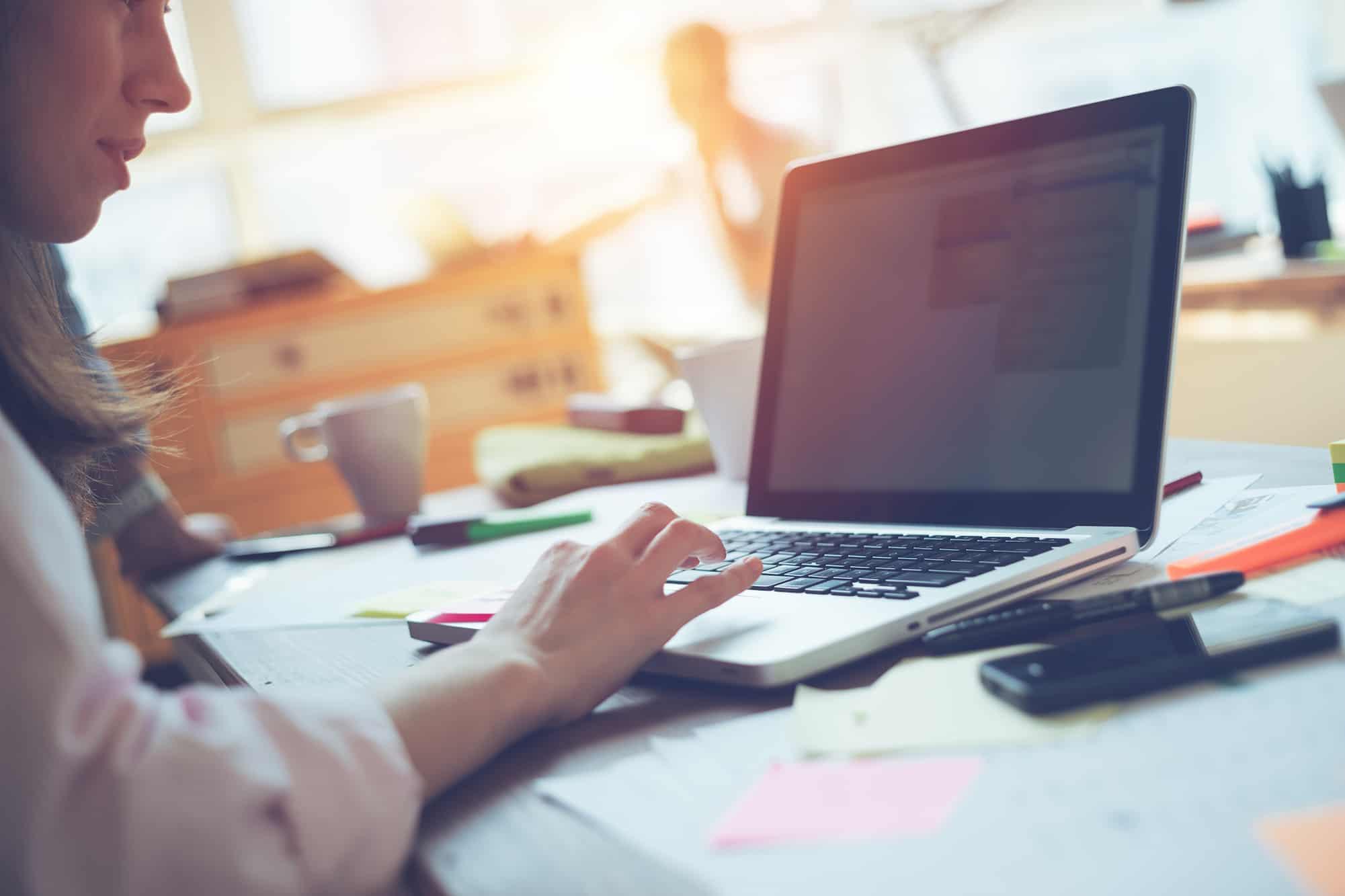 Kvinnlig regnskapsfører som jobber hos et regnskapsbyrå med en Apple laptop